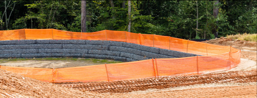 An orange safety fence surrounding a work area