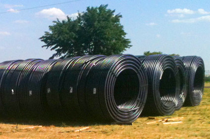Large HDPE pipe rolls stacked on jobsite