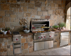An outdoor grill with cabinets and storage areas