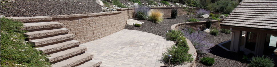 A backyard with stone retaining walls, stone steps, and a stone patio