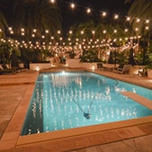 A pool area with overhead light strands