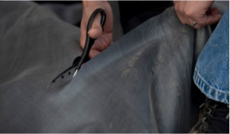 Shears cutting a pond liner