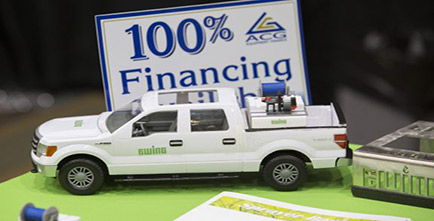 Image of a truck in front of a 100% financing sign