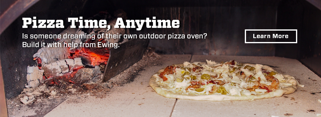 an Uncooked pizza on grey concrete slab with burning coals in corner of a pizza stove box