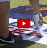 A screen shot of someone painting a field with a stencil