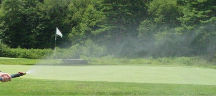 A nozzle spraying water on a golf course